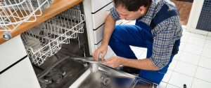 dishwasher repair man repairing a dishwasher